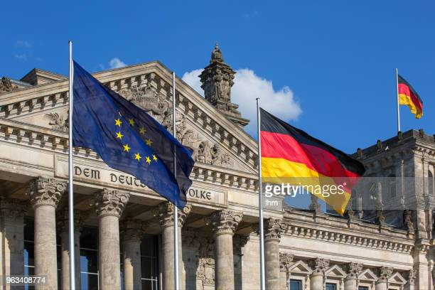 reichstag building in berlin with german and eu-flag (berlin, germany) - europäische kultur stock-fotos und bilder