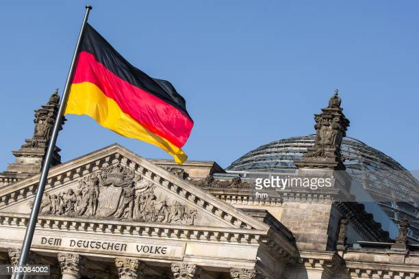 """reichstag building-  inscription on the architrave  """"dem deutschen volke"""" with german flag (berlin, germany) - reichstag stock-fotos und bilder"""