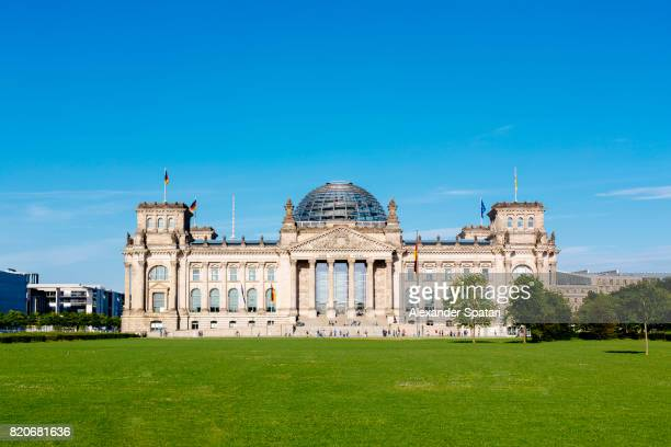 Reichstag building on a sunny day with clear blue sky and lawn with green grass