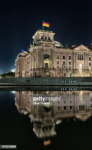reichstag building reflecting in spree river at night, berlin, germany - reichstag stock-fotos und bilder