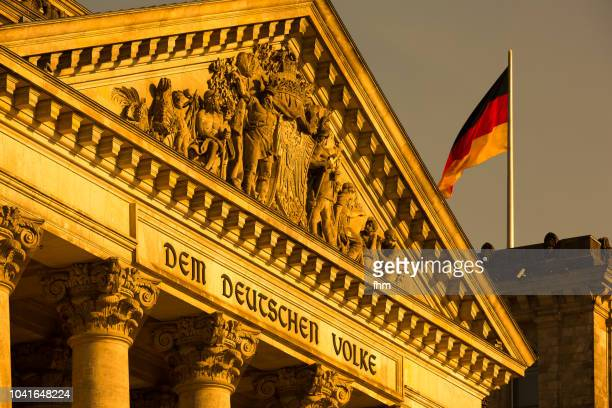 Reichstag building - the famous inscription on the architrave on the west portal of the Reichstag building in Berlin: 'Dem Deutschen Volke' with german flag (Germany)