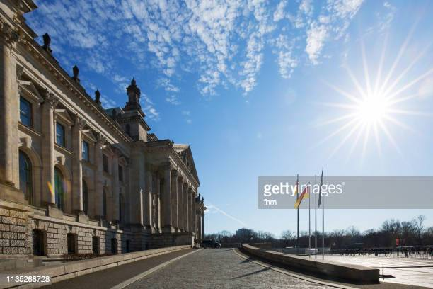 Reichstag building with bright sun (german parliament building) - Berlin, Germany
