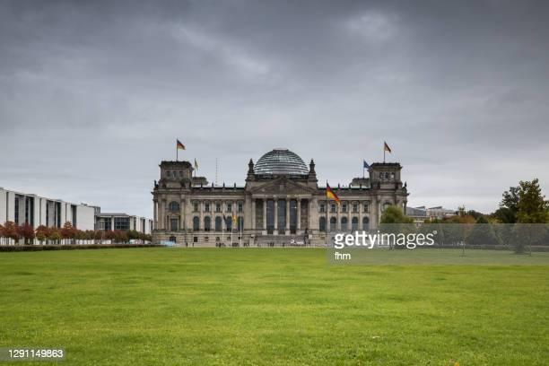 reichstag building with dark clouds (deutscher bundestag, berlin/ germany) - reichstag stock-fotos und bilder