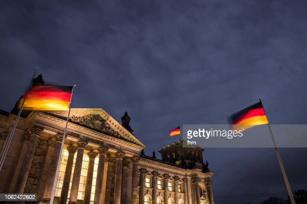 reichstag building with german flags at blue hour (germany) - bundestag stock photos and pictures