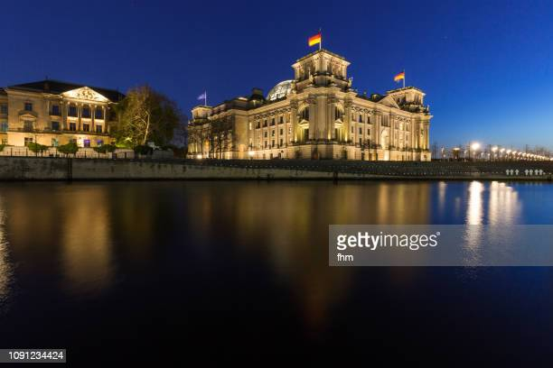 Reichstag building with german flags at blue hour (Germany)