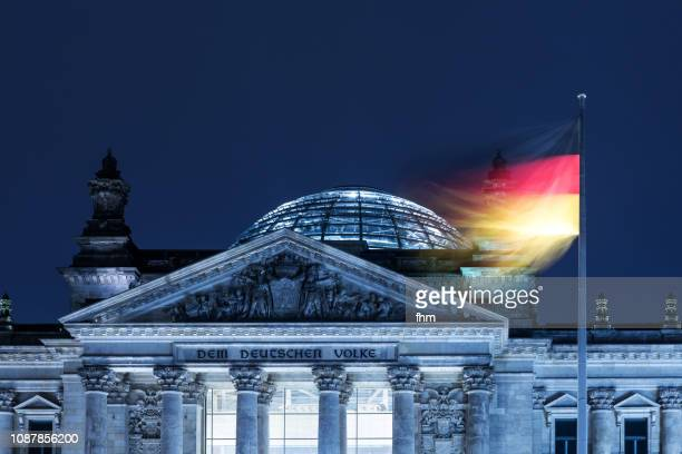 Reichstag building with inscription on the west portal 'Dem Deutschen Volke' with german flag (Berlin, Germany)