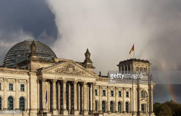 reichstag building with rainbow (german parliament building) in the german capital berlin - reichstag stock-fotos und bilder