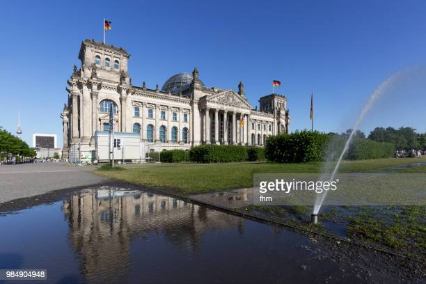 Reichstag building with reflection in a puddle and sprinkler (German parliament building) - Berlin, Germany