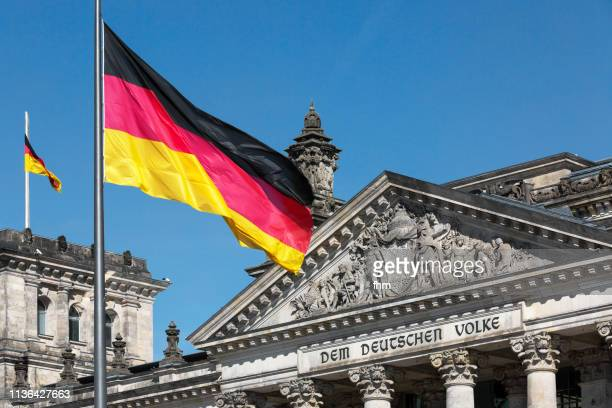 Reichstag building with the famous inscription on the architrave on the west portal of the Reichstag building in Berlin: 'Dem Deutschen Volke' with german flag (Germany)