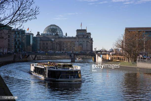 Reichstag building with tourboat on Spree river(german parliament building) - Berlin, Germany
