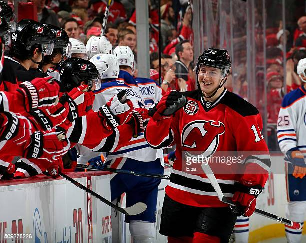 Reid Boucher of the New Jersey Devils is congratulated by teammates on the bench after he scored the game winnign goal in the third period against...