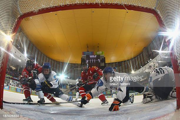Reid Gardiner Eric Cornel of Canada and Kasperi Kapanen Markus Haapanen of Finland challenged for the puck during the men's semi final ice hockey...