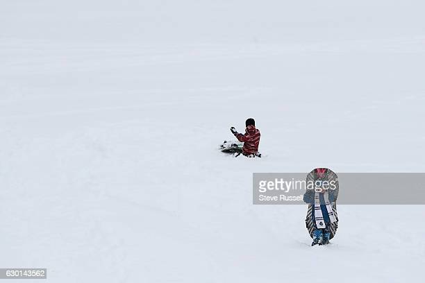Reid Kyer behind the long climb up the hill as his brother Everett picks up snow in Riverdale Park as Toronto digs out, copes and enjoys the first...