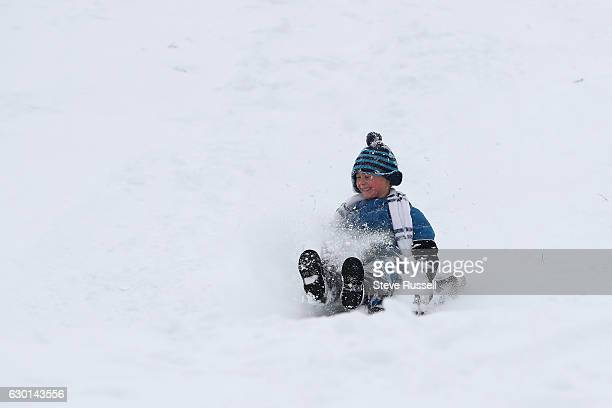 Reid Kyer sleds down the fresh powder on the hill in Riverdale Park as Toronto digs out, copes and enjoys the first big overnight snowfall of the...