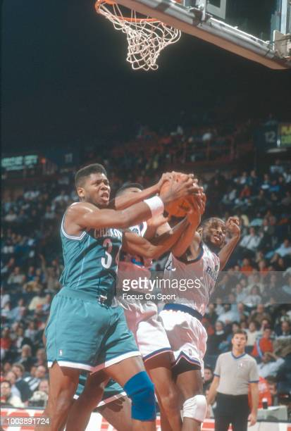 R Reid of the Charlotte Hornets battles for a rebound with Pervis Ellison of the Washington Bullets during an NBA basketball game circa 1991 at the...