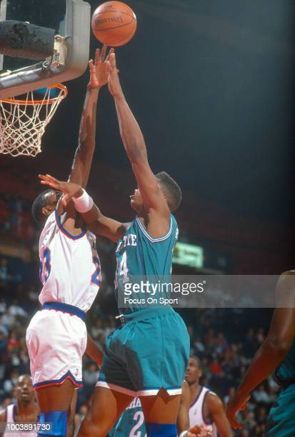 R Reid of the Charlotte Hornets shoots over Charles Jones of the Washington Bullets during an NBA basketball game circa 1991 at the Capital Centre in...
