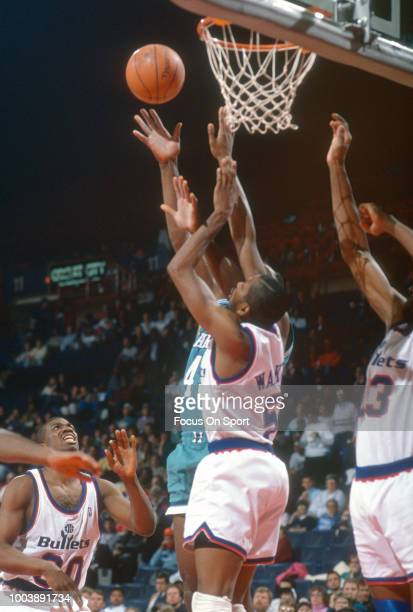 R Reid of the Charlotte Hornets shoots over Darryl Walker of the Washington Bullets during an NBA basketball game circa 1991 at the Capital Centre in...
