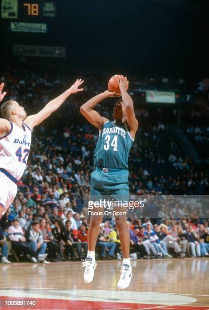R Reid of the Charlotte Hornets shoots over Mark Acres of the Washington Bullets during an NBA basketball game circa 1992 at the Capital Centre in...