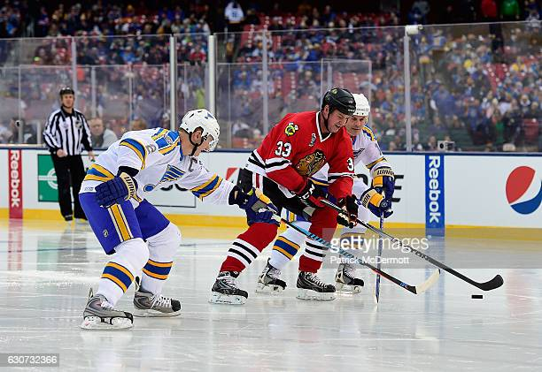 Reid Simpson of the Chicago Blackhawks skates the puck between Al MacInnis and Adam Oates of the St Louis Blues during the 2017 Bridgestone NHL...