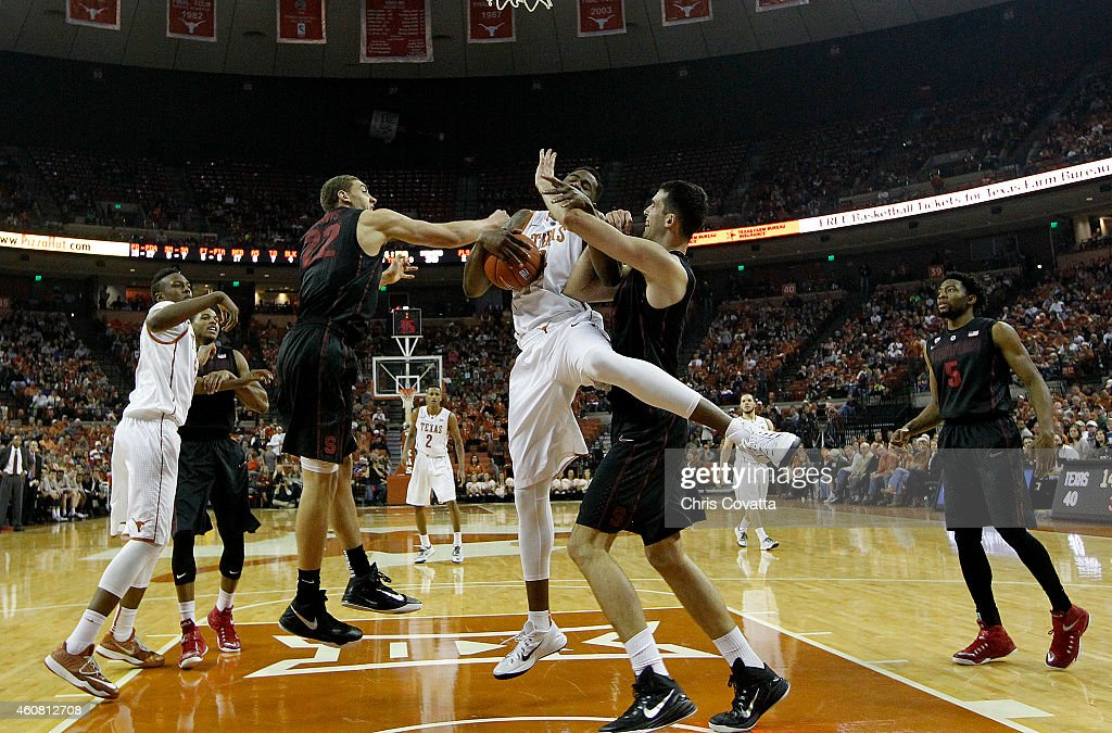 Reid Travis #22 and Stefan Nastic #4 of the Stanford Cardinal fight Prince Ibeh #44 of the Texas Longhorns for the ball at the Frank Erwin Center on December 23, 2014 in Austin, Texas.