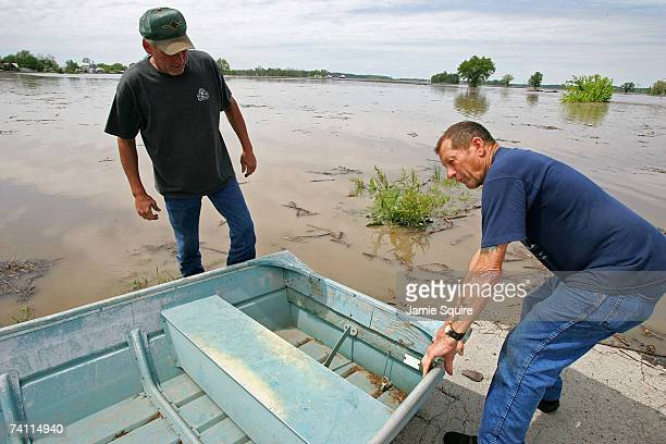 Reid White helps Larry Turner take a boat off Turner's truck as Turner prepares to inspect damage to his flooded farm after heavy rains caused the...
