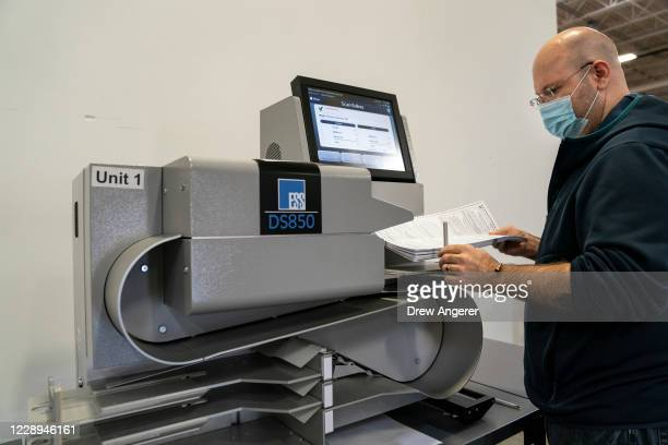 Reider White II, the voting systems manager, feeds mail-in ballots into a high speed ballot scanner to be tabulated in a warehouse at the Anne...