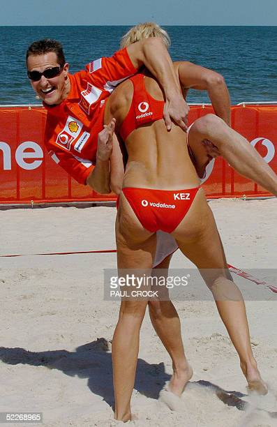 Reiging Formula One World Champion Michael Schumacher of Germany wrestles with Olympic Beach Volleyball Gold Medalist Kerri Pottharst of Australia...