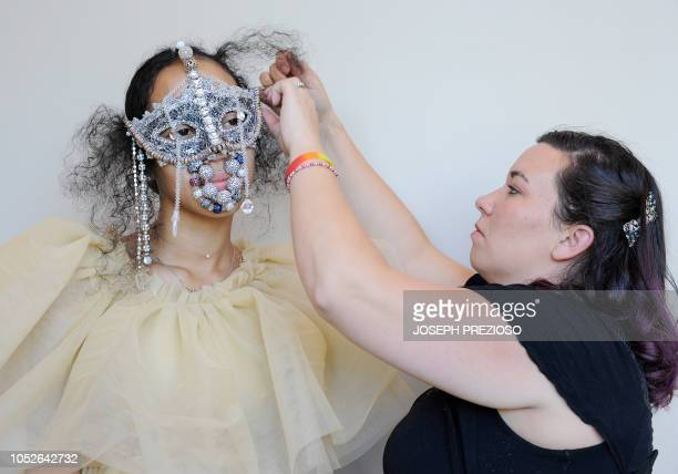 Reignie St Pierre gets fitted with her face mask during the 3018 fashion show at the 12th Annual Black New England Conference at the University of...