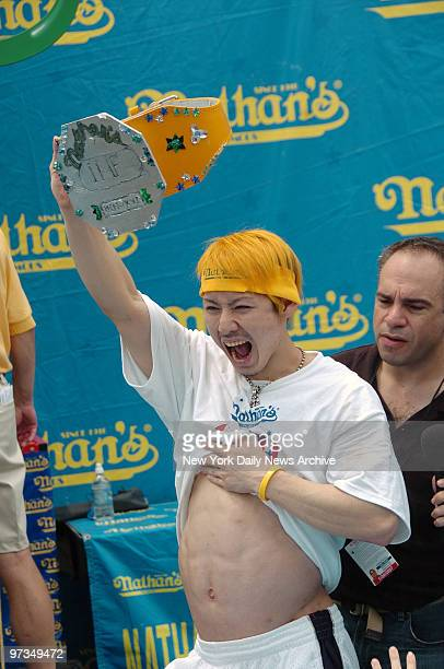 Reigning champion Takeru Kobayashi shows off his bulging belly as he holds the Mustard Belt after winning Nathan's Famous Fourth of July...