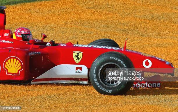 Reigning five-time World Champion Michael Schumacher of Germany limps back to the pits after crashing his Ferrari into the safety barrier during the...
