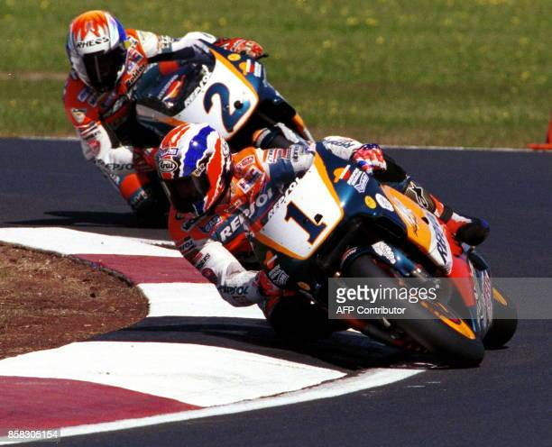 Reigning fourtime World Champion Michael Doohan of Australia leads Honda teammate Tadayuki Okada of Japan out of the hairpin corner during the final...