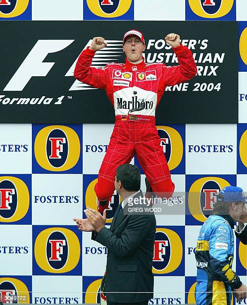 Reigning sixtime World Champion Michael Schumacher of Germany leaps in the air on the podium watched by Victorian state premier Steve Bracks after...
