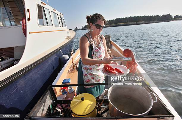Reilly Harvey pulls a cooked lobster from a pot onboard her boat Mainstay Saturday, July 26, 2014 in the harbor between Dix Island and High Island,...