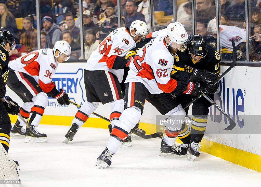Reilly Smith #18 of the Boston Bruins battles Eric Gryba #62 of the Ottawa Senators during an NHL hockey game on December 13, 2014 at TD Garden in Boston, Massachusetts.