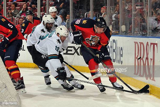 Reilly Smith of the Florida Panthers digs the puck out from the boards against Patrick Marleau of the San Jose Sharks and teammate Joel Ward at the...