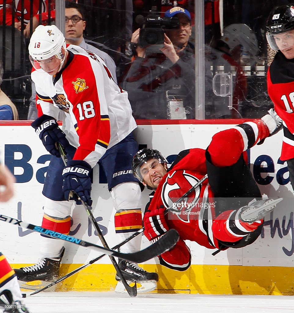Reilly Smith #18 of the Florida Panthers takes down Stephen Gionta #11 of the New Jersey Devils on a bodycheck during the third period of an NHL hockey game at Prudential Center on December 6, 2015 in Newark, New Jersey. Devils on 4-2.
