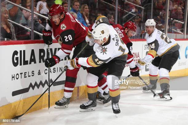 Reilly Smith of the Vegas Golden Knights attempts to control the puck from Dylan Strome of the Arizona Coyotes during the second period of the NHL...