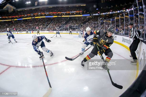 Reilly Smith of the Vegas Golden Knights plays the puck along the boards away from Josh Morrissey and Jacob Trouba of the Winnipeg Jets during second...