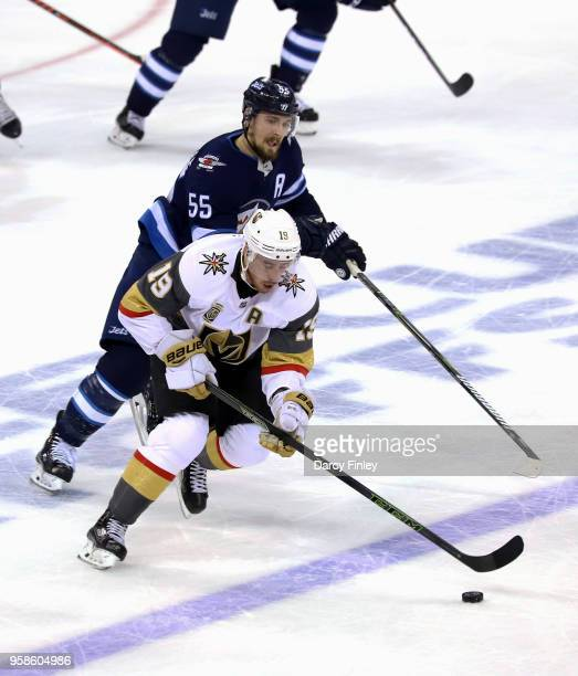 Reilly Smith of the Vegas Golden Knights plays the puck down the ice as Mark Scheifele of the Winnipeg Jets gives chase during second period action...