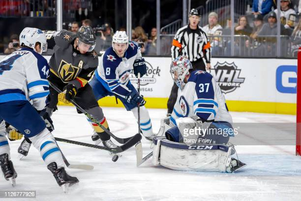 Reilly Smith of the Vegas Golden Knights plays the puck towards the goal as goaltender Connor Hellebuyck Josh Morrissey and Jacob Trouba of the...