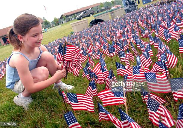 Reilly Weiser of Croydon Pennsylvania places American flags in the ground while setting up the Donald W Jones Flag Memorial 13 2003 in Fairless Hills...