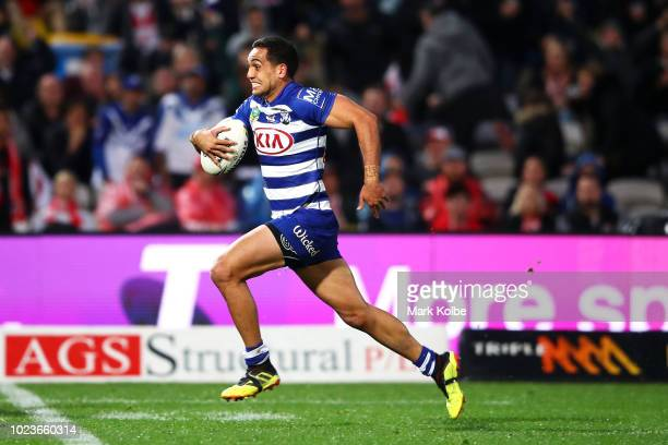 Reimis Smith of the Bulldogs breaks away to score a try during the round 24 NRL match between the St George Illawarra Dragons and the Canterbury...
