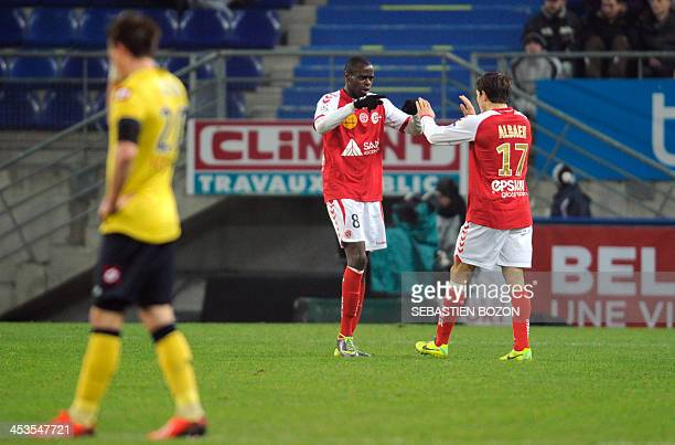 Reims' Congolese midfielder Prince O'Niangue celebrates with Danish midfielder Mads Albaek after scoring a goal during the French L1 football match...