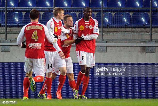 Reims' Congolese midfielder Prince O'Niangue celebrates with teammates after scoring a goal during the French L1 football match between Sochaux and...