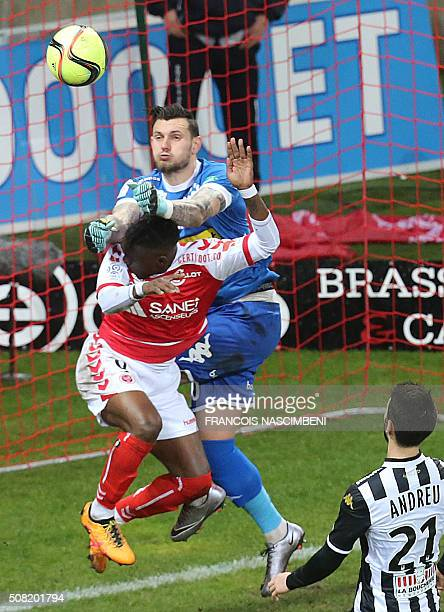 Reims' Congolese Thievy Bifouma vies with Angers' French goalkeeper Alexandre Letellier during the French Ligue 1 football match between Reims and...