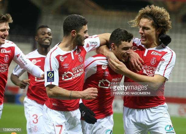 Reims' defender Mathieu Cafaro is congratulated by teammates after scoring a goal during the French L1 football match between Stade de Reims and AS...