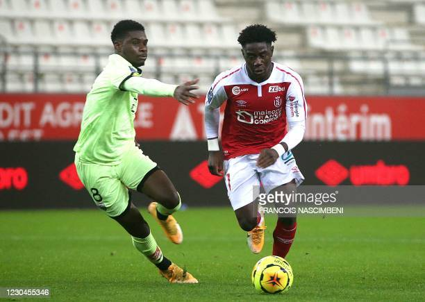 Reims' forward Boulaye Dia fights for the ball with Dijon's midfielder Eric Dina Ebimbe during the French L1 football match between Stade de Reims...