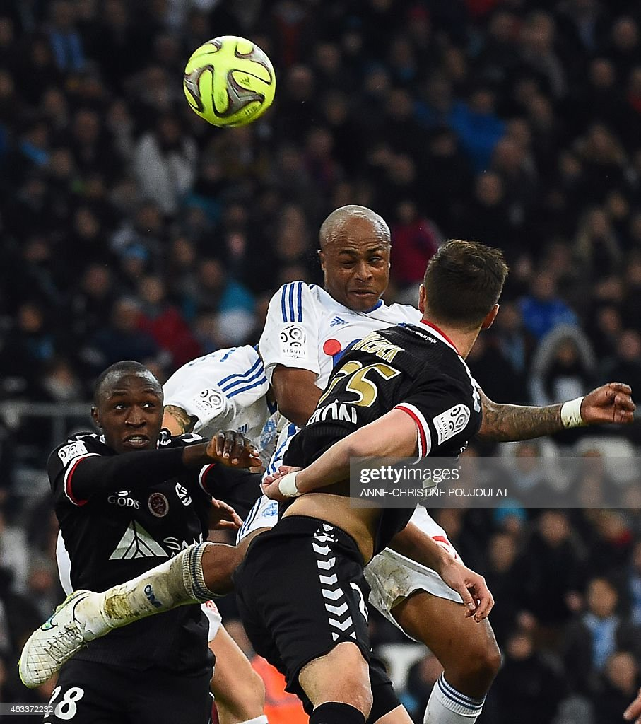 Reims' French defender Antoine Conte (L) vies with Marseille's Ghanaian forward Andre Ayew (R) during the French L1 football match Marseille vs Reims on February 13, 2015 at the Velodrome stadium in Marseille, southern France.