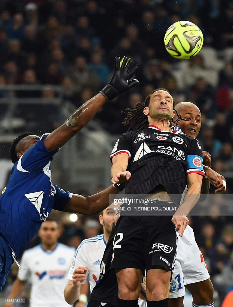 Reims' French defender Mickael Tacalfred (L) vies with Marseille's Ghanaian forward Andre Ayew during the French L1 football match Marseille vs Reims on February 13, 2015 at the Velodrome stadium in Marseille, southern France.