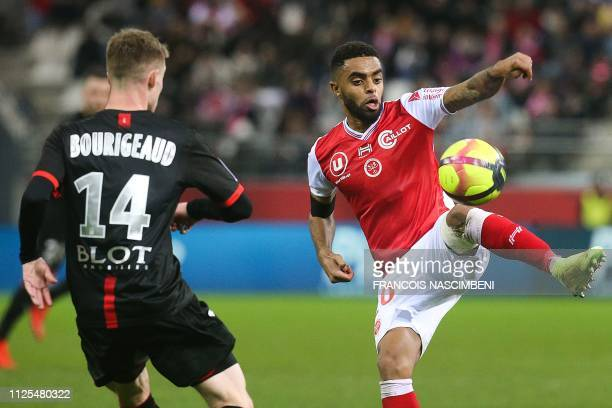Reims' French midfielder Tristan Dingome vies for the ball with Rennes' midfielder Benjamin Bourigeaud during the French L1 football match between...